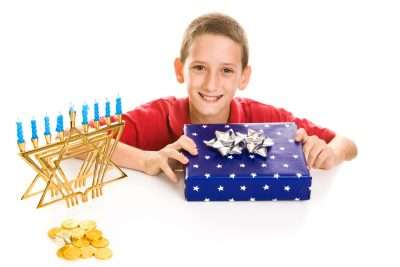 Happy little boy excited about opening his hanukkah gift. Isolated on white.